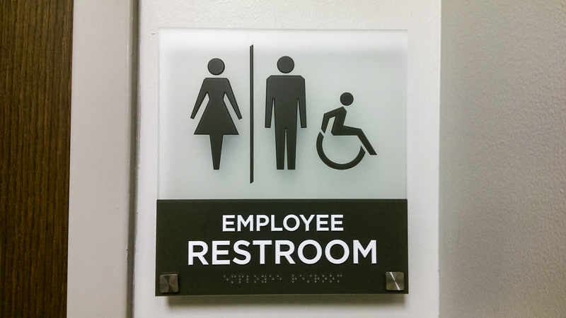 Interior ADA compliant restroom signage for Sacred Heart Health System. Fabricated and installed by Signgeek.